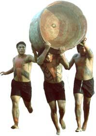 imagem de três índios em uma competião carregando o tronco